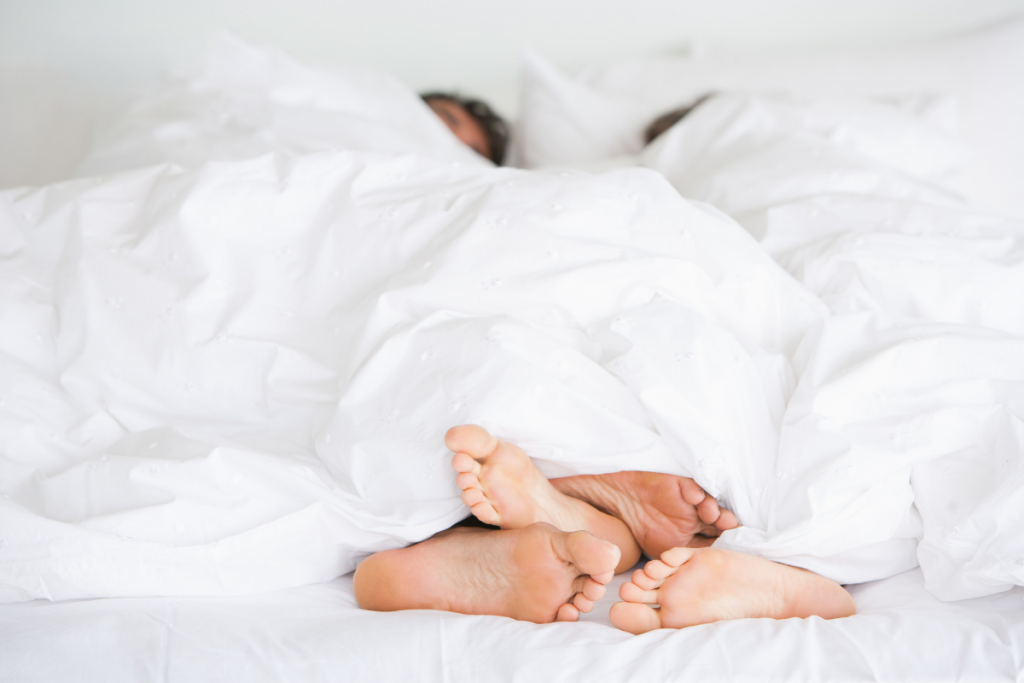 couple lying in bed under what could be a CosyCool duvet