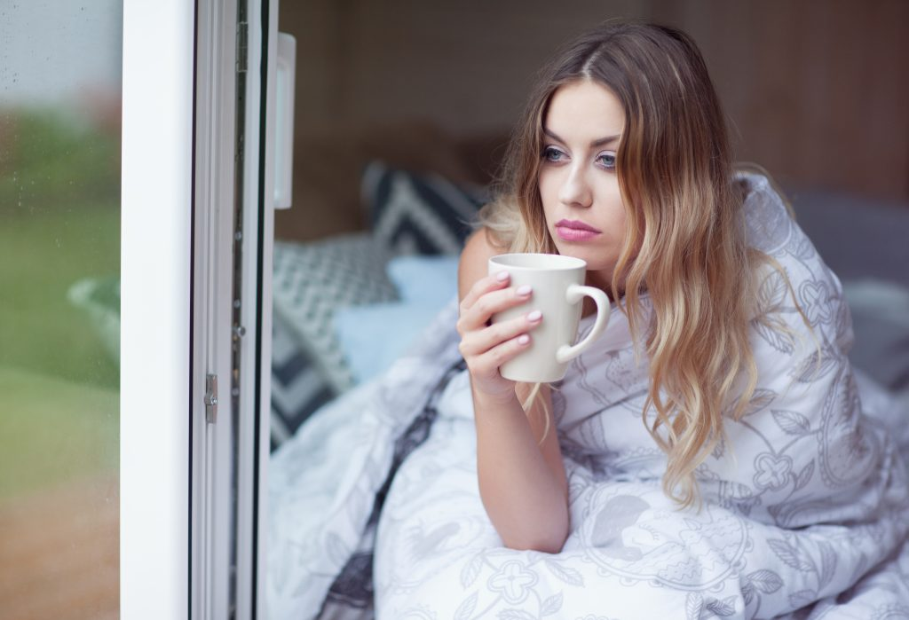 Lady drinking coffee taking the day off work wrapped in what could be a CosyCool duvet